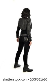 full length portrait of black haired girl wearing leather outfit, standing pose facing away from camera.  isolated on white background.