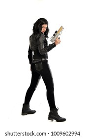full length portrait of black haired girl wearing leather outfit. standing pose  and holding a gun on a white background.