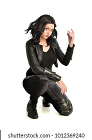 full length portrait of black haired girl wearing leather outfit. seated pose while holding a gun, isolated on a white studio background.