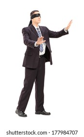 Full length portrait of a blindfolded businessman in suit isolated on white background