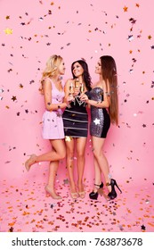Full length portrait of blonde brunette attractive sexy girls in gold confetti celebrating birthday night, bachelor party, holding stemware with champagne, looking to each other, pink background