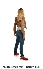 full length portrait of blonde girl wearing simple brown jacket and jeans, standing pose wit back to the camera. isolated on white background.