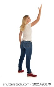 full length portrait of blonde girl wearing simple white shirt and jeans. standing pose wit back to the camera, isolated on studio background.