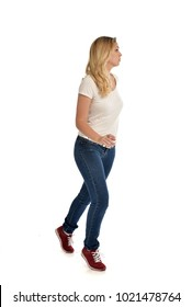 full length portrait of blonde girl wearing white shirt and jeans, standing pose on studio background.