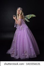 full length portrait of a blonde girl wearing a fantasy fairy inspired costume,  long purple ball gown with fairy wings.   standing pose, with back to the camera on a dark studio background.