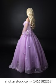 full length portrait of a blonde girl wearing a fantasy fairy inspired costume,  long purple ball gown,  standing pose with back to the camera on a dark studio background.