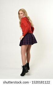 full length portrait of blonde girl wearing red cardigan with tie and plaid skirt, school uniform, standing pose facing away from the camera, on a white studio background.