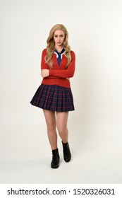 full length portrait of blonde girl wearing red cardigan with tie and plaid skirt, school uniform, standing,  walking  pose facing the camera, on a white studio background.