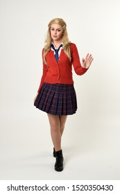 full length portrait of blonde girl wearing red cardigan with tie and plaid skirt, school uniform, standing,  walking  pose facing the camera, on a white studio background
