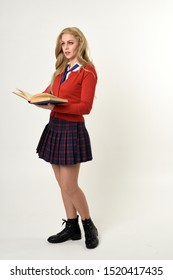 full length portrait of blonde girl wearing red cardigan with tie and plaid skirt, school uniform, standing  pose holding books,  facing the camera, on a white studio background.