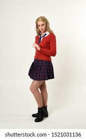 full length portrait of blonde girl wearing red cardigan with tie and plaid skirt, school uniform, side profile, standing  pose, on a white studio background.