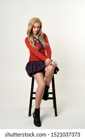 full length portrait of blonde girl wearing red cardigan with tie and plaid skirt, school uniform. Sitting on a chair with  a white studio background.