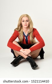 full length portrait of blonde girl wearing red cardigan with tie and plaid skirt, school uniform. Sitting on the ground with  a white studio background.