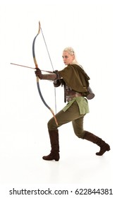 full length portrait of a blonde girl wearing green and brown medieval costume, holding a bow and arrow.