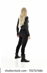 full length portrait of blonde girl wearing black leather outfit, standing pose, isolated on white background.