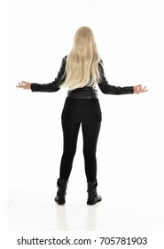 full length portrait of blonde girl wearing black leather outfit, standing pose on white background.