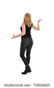 full length portrait of blonde girl wearing black clothes and boots. standing pose on white background.