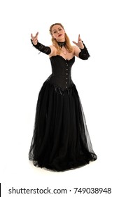 full length portrait of a blonde girl wearing black gothic gown. standing pose, isolated on white background.