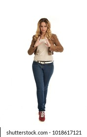 full length portrait of blonde lady wearing simple brown jacket and jeans, standing pose isolated on white studio background.
