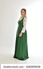 full length portrait of blonde lady wearing green fantasy, medieval gown. standing pose on white background.