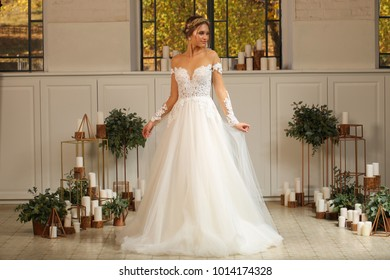 Full length portrait of a blonde woman wearing full length white gown and corset