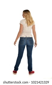 full length portrait of blonder wearing white shirt and jeans, standing pose on studio background.