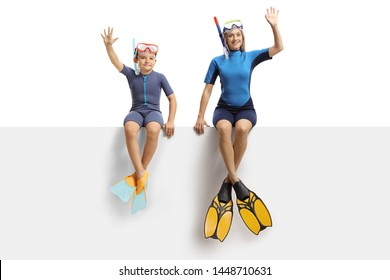 Full length portrait of a boy and a woman on a panel waving and wearing a wetsuit, a diving mask and diving flippers isolated on white background