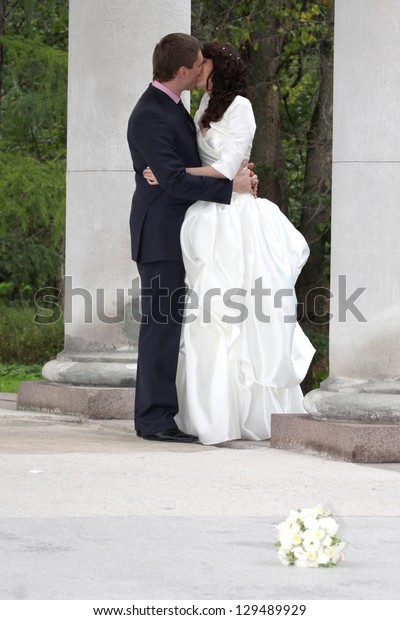 Full length portrait of bride and groom kissing near columns in park