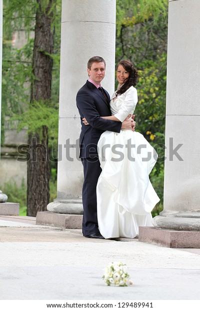 Full length portrait of bride and groom near columns in park
