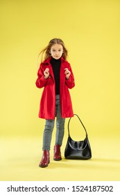 A full length portrait of a bright fashionable girl in a red raincoat with black bag posing on yellow studio background. Looks happy. Autumn and spring fashion for kids. Cute stylish blonde girl.