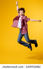 A full length portrait of a bright young boy jumping in the studio over the yellow background. Kids, fashion.