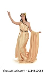 full length portrait of brunette girl wearing golden fantasy toga.   standing pose on white background.