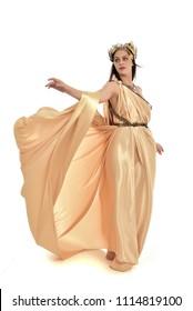 full length portrait of brunette girl wearing golden fantasy toga.   standing pose on white background.