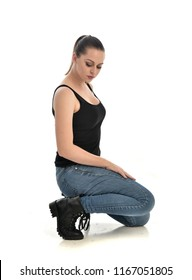 full length portrait of brunette girl wearing black singlet and jeans. seated pose. isolated on white studio background.