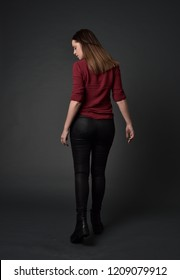 full length portrait of brunette girl wearing red shirt and leather pants. standing pose with back to the camera. grey studio background.