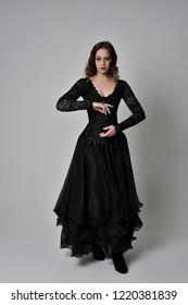 full length portrait of brunette girl wearing long black lace gown. standing pose on grey studio background.