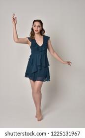 full length portrait of brunette girl wearing short blue dress. grey studio background.