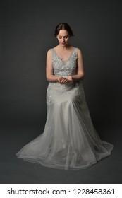 full length portrait of brunette girl wearing beautiful long gown. posing against a grey studio background.