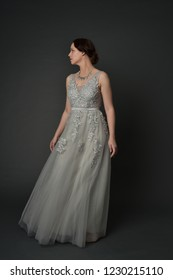full length portrait of brunette  girl wearing long silver ball gown. standing pose on grey studio background.