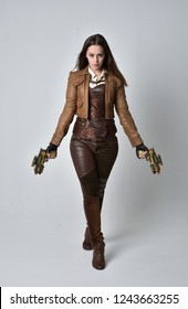 full length portrait of brunette  girl wearing brown leather steampunk outfit. standing pose, holding a gun, on grey studio background.
