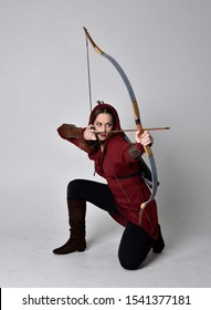 full length portrait of a brunette girl wearing a red fantasy tunic with hood, holding a bow and arrow. Standing pose on a white studio background.