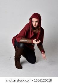 full length portrait of a brunette girl wearing a red fantasy tunic with hood. Seated pose on a white studio background.