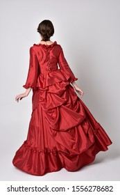 full length portrait of a brunette girl wearing a red silk victorian gown. Standing pose with back to the camera on a white studio background.
