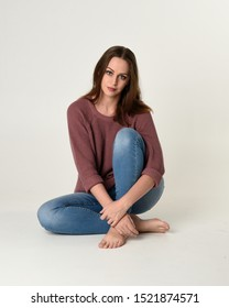 full length portrait of brunette woman wearing jeans and pink jumper. seated pose with a white studio background.