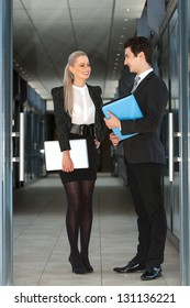 Full length portrait of business couple with file and laptop.