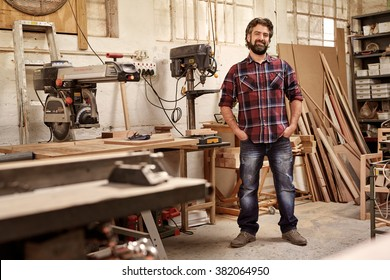 Full length portrait of a business owner who runs a carpentry studio, standing confidently with his hands in his pockets, smiling at the camera, in workshop with pieces of wood and woodwork machinery