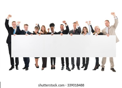 Full length portrait of business team with arms raised holding blank billboard against white background
