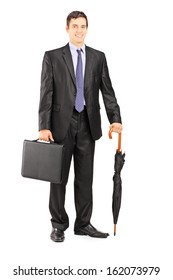 Full length portrait of a businessman in black suit holding an umbrella and briefcase isolated on white background