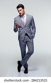 Full length portrait of a businessman standing with smartphone over gray background and looking at camera