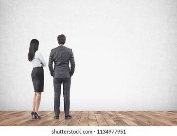 Full length portrait of a businesswoman and a businessman looking at a blank concrete wall in front of them. Formal wear. Copy space mock up Advertising and marketing.